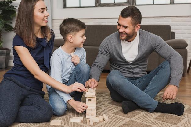 Retrato de pais adoráveis brincando com filho
