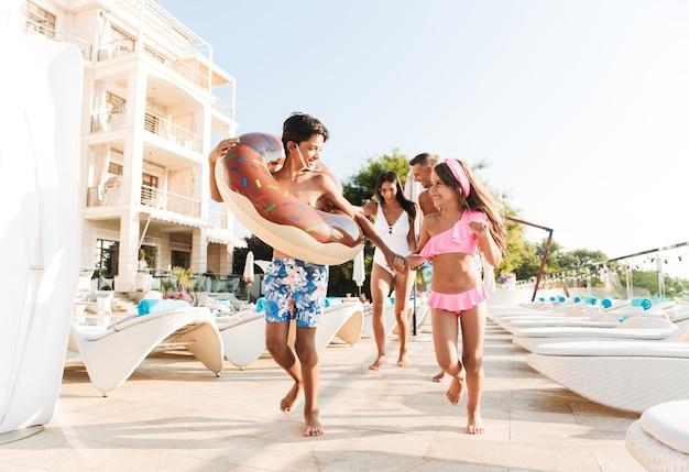 Retrato de pais e crianças sorridentes, caminhando perto da piscina e carregando um anel de borracha fora do hotel durante as férias