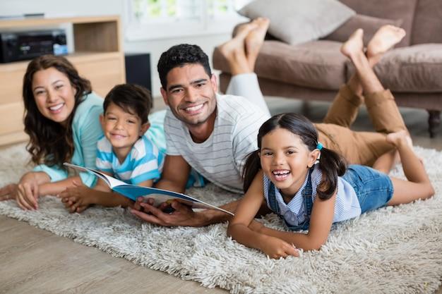 Retrato de pais e filhos, deitado no tapete e livro de leitura