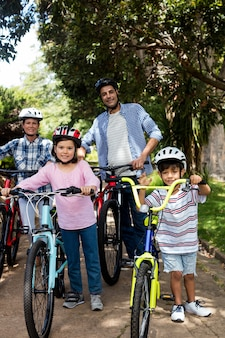 Retrato de pais e filhos em pé com bicicleta no parque