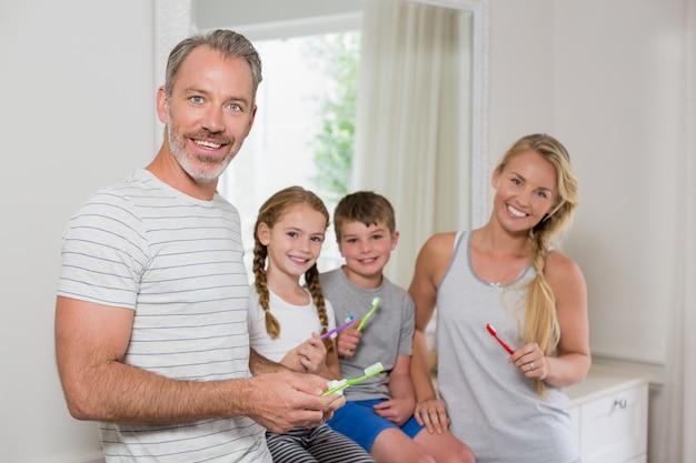 Retrato de pais e filhos escovando os dentes no banheiro