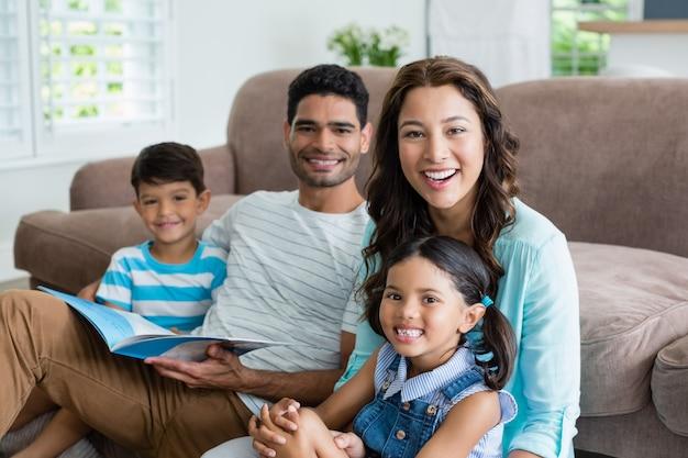Retrato de pais e filhos sentados no sofá e lendo o livro