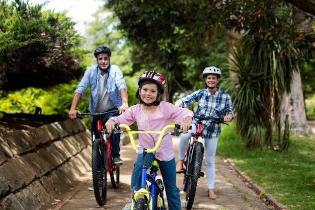 Retrato de pais felizes e filha em pé com bicicleta no parque