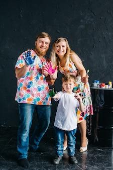Retrato de pais felizes fofos com crianças pintando e se divertindo. eles mostram as mãos pintadas em cores brilhantes. ficamos em casa e nos divertimos.