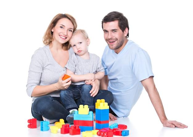Retrato de pais jovens felizes e sorridentes, brincando com um bebê - isolado no branco