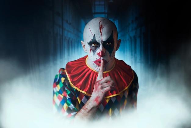 Retrato de palhaço louco sangrento mostra o sinal de silêncio, rosto com sangue. homem maquiado com fantasia de halloween, louco maníaco