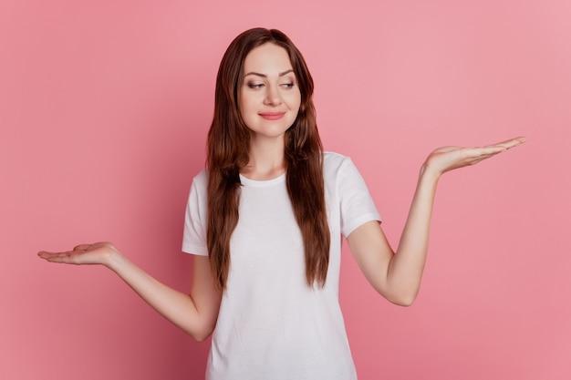 Retrato de palmas de menina encantadora e sugestiva segurando conceito de escalas de espaço vazio em fundo rosa
