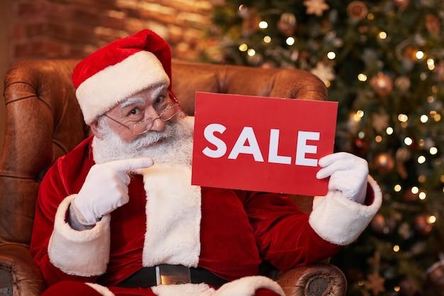 Retrato de papai noel barbudo positivo em óculos, sentado na poltrona e apontando para o banner de venda