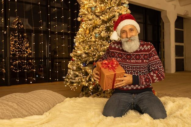 Retrato de papai noel feliz em seu quarto em casa perto da árvore de natal.