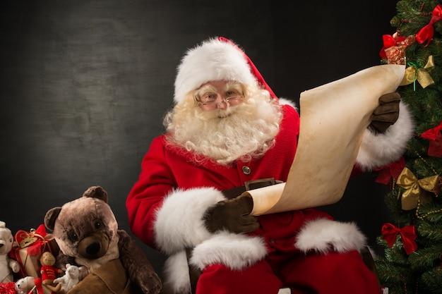 Retrato de papai noel feliz lendo carta de natal ou lista de desejos