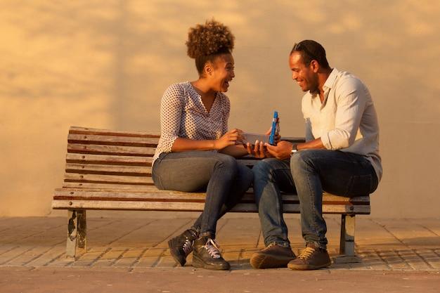 Retrato, de, par feliz, sentar-se banco, com, homem, dar, presente aniversário