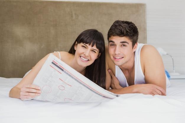 Retrato, de, par, jornal leitura, cama, em, quarto