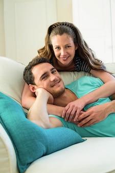 Retrato, de, par jovem, abraçar, ligado, sofá, em, sala de estar