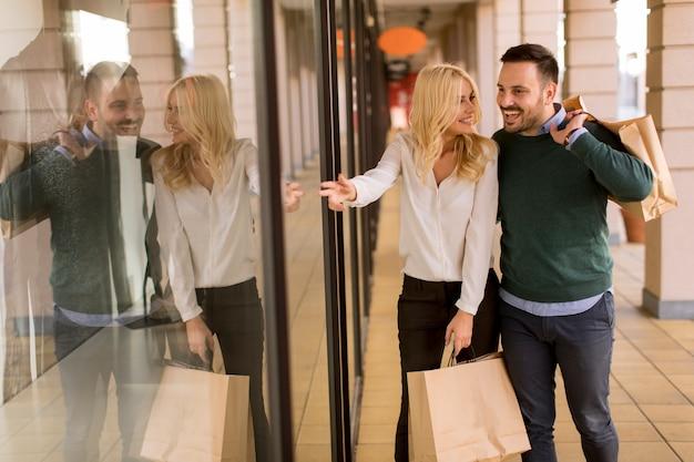 Retrato, de, par jovem, com, bolsas para compras, em, cidade