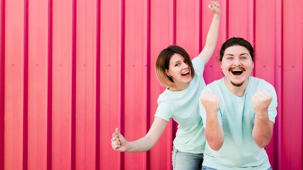 Retrato, de, par jovem, desfrutando, com, alegria, contra, vermelho, ondulado, fundo