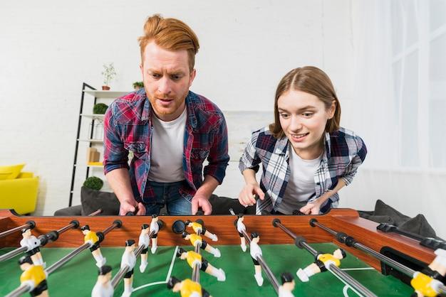 Retrato, de, par jovem, desfrutando, jogando futebol, jogo, casa