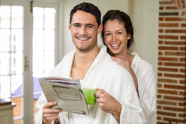 Retrato, de, par jovem, em, bathrobe, tendo, chá, e, jornal leitura, em, cozinha