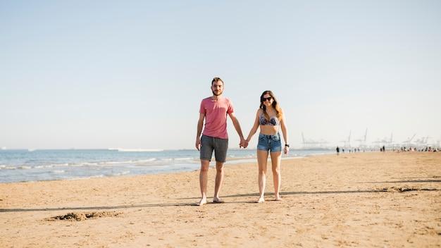 Retrato, de, par jovem, segurando, cada, outro, mão, desfrutando, em, praia