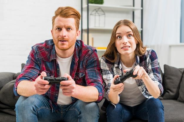 Retrato, de, par jovem, sentar sofá preto, videogame jogando, com, joystick