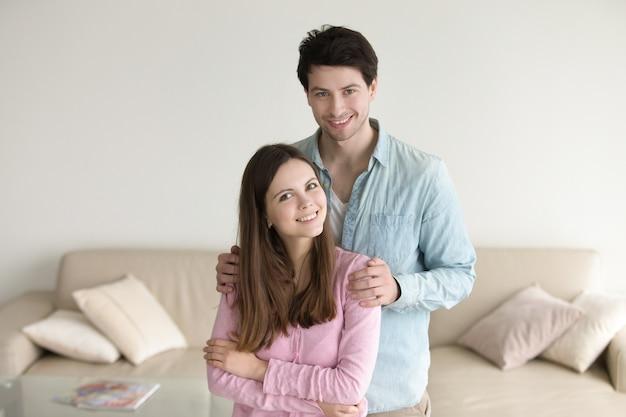 Retrato, de, par jovem, sorrindo, abraçar, casa