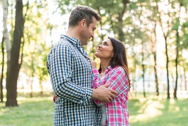 Retrato, de, par romântico, olhando um ao outro, enquanto, abraçar, parque