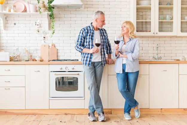 Retrato, de, par velho, segurando, wineglasses, em, mão, olhando um ao outro, ficar, em, cozinha