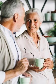 Retrato, de, par velho, xícara segurando café, olhando um ao outro