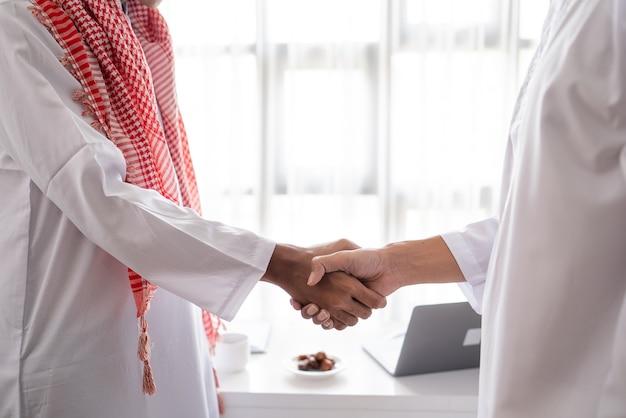 Retrato de parceiro muçulmano de negócios apertando a mão na reunião