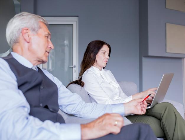 Retrato de parceiros de negócios inteligente olhando para laptop