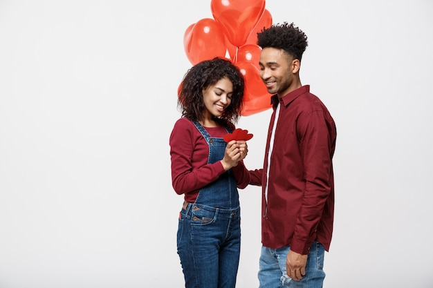 Retrato de pares novos no amor que guarda o coração e o balão de papel vermelhos.