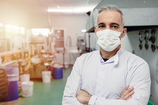 Retrato de pé de meia-idade 40-50 do trabalhador europeu altamente qualificado de confiança na fábrica com máscara facial.