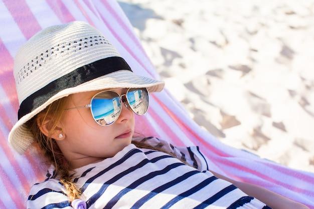 Retrato, de, pequeno, adorável, menina, mentindo, ligado, praia, lounger
