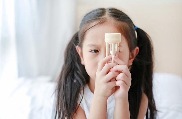 Retrato, de, pequeno, menina asiática, olhar, ampulheta, em, mão, encontrar-se cama, casa