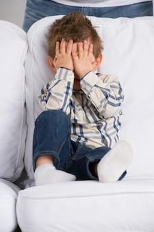 Retrato de pequeno menino fechando os olhos com as mãos em casa