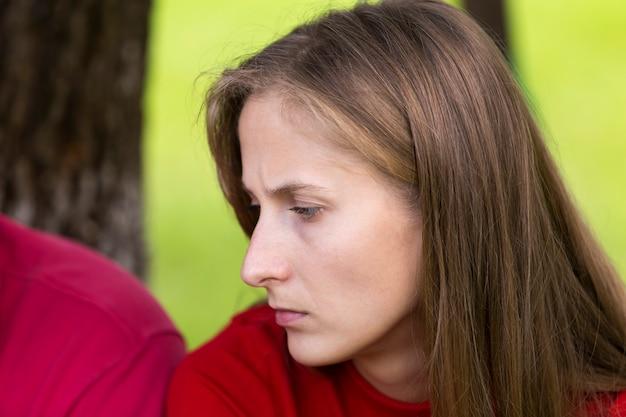 Retrato de perfil de close-up da jovem mulher loira atraente cabelos compridos temperamental triste pensamento infeliz