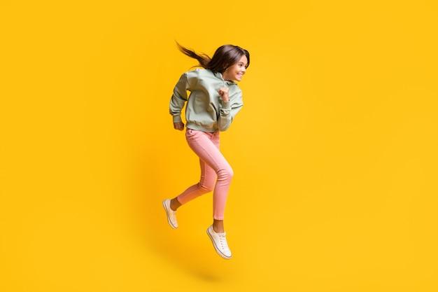 Retrato de perfil de corpo inteiro de aluno pulando o punho no ar, isolado em um fundo de cor amarela vibrante