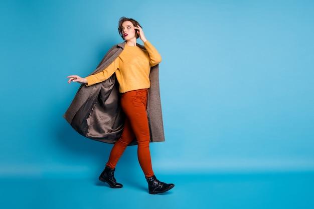 Retrato de perfil de corpo inteiro de uma senhora deslumbrante caminhada pela rua viagem viajando para o exterior tendência olhar vestir calças de casaco longo casual elegantes.