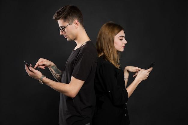 Retrato de perfil de jovem casal, navegando informações em seus pdas