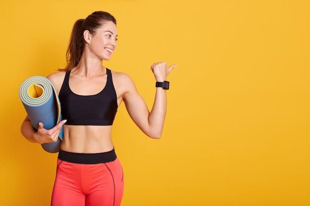 Retrato de perfil de jovem segurando a esteira e mostra os músculos, desportivo feminino olhando de lado, vestindo roupas esportivas elegantes