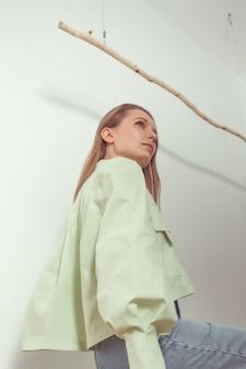 Retrato de perfil de mulher inteligente caucasiana atraente em um vestido verde de algodão e calça jeans em um quarto feito em estilo escandinavo.