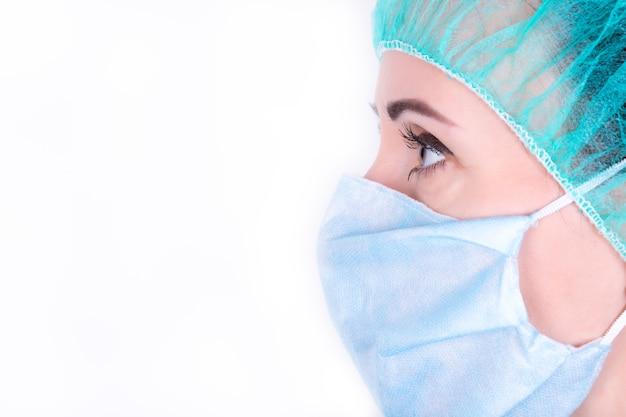 Retrato de perfil de parte de close-up do jovem médico feminino na tampa médica, máscara na parede azul com espaço para texto. médica na clínica. coronavirus epidemic pandemic, covid-19. conceito de ficar em casa