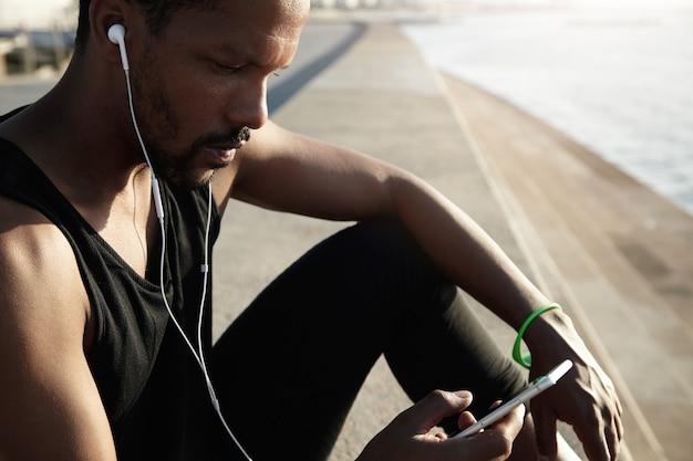Retrato de perfil de trabalhador de escritório preto em fones de ouvido descansando após seu treinamento matinal ao ar livre, ouvindo música, olhando para a tela do seu telefone inteligente e escolhendo músicas favoritas da lista de faixas