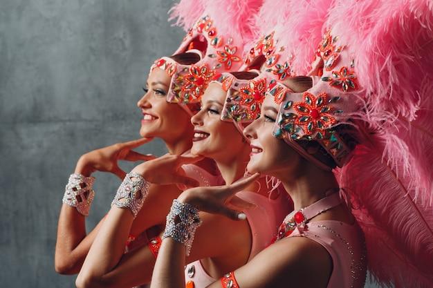 Retrato de perfil de três mulheres em traje de samba ou lambada com plumagem de plumas rosa