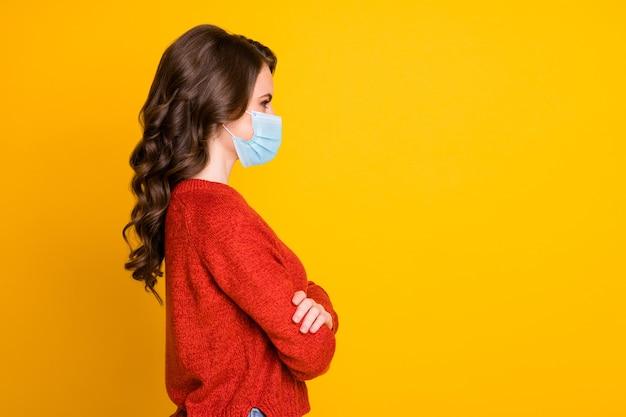 Retrato de perfil dela, vista lateral, linda, adorável, alegre, de cabelos ondulados, braços cruzados, olhar de primavera, usar máscara médica isolada brilho vívido amarelo cor de fundo