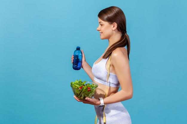 Retrato de perfil feliz, saudável, magro, mulher, segurando uma garrafa com água e salada, nutrição saudável