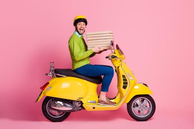 Retrato de perfil lateral de um cara dirigindo uma motocicleta trazendo uma torta saborosa