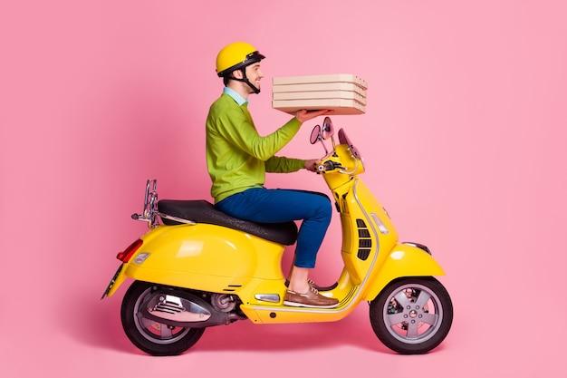 Retrato de perfil lateral de um cara dirigindo uma motocicleta trazendo uma torta