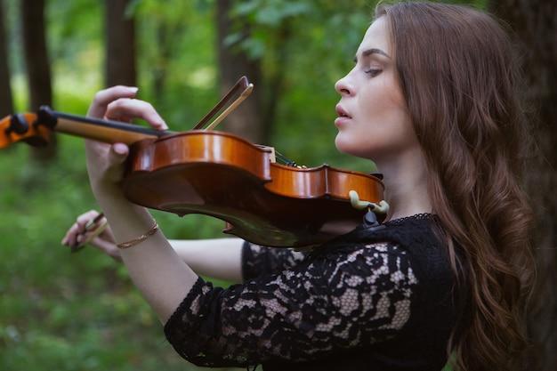 Retrato de perto de uma jovem violinista que toca violino com entusiasmo em uma obra romântica no parque
