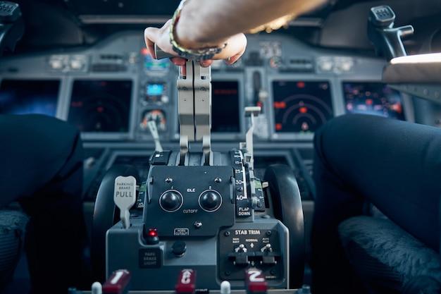 Retrato de perto do braço do piloto está controlando o avião para decolar e pousar