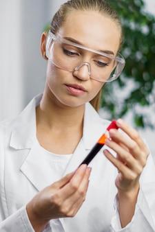 Retrato de pesquisadora em laboratório com óculos de segurança e tubo de ensaio